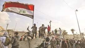 Iraqi protesters wave the national flag amid clashes with riot police following a demonstration at B