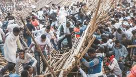 A crowd removes scaffoldings of a structure that collapsed, trapping and injuring dozens of people,
