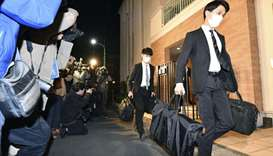 Officials from the Tokyo District Public Prosecutors Office carry bags after raiding the Tokyo resid