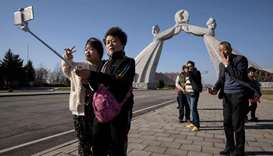 Tourists from China pose for photos before the Three Charters monument in Pyongyang on April 15, 201