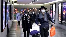 People wearing masks walk through an underground passage to the subway in Beijing, China