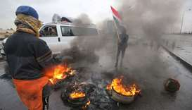 Iraqi protesters wave their national flag near burning tyres during ongoing demonstrations on Mohamm