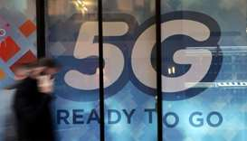 A man walks past a 5G sign