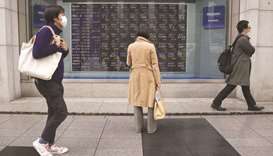 A pedestrian looks at an electronic stock board outside a securities firm in Tokyo. Japanese shares