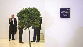 People stand behind a tree installed as decoration inside the Congress centre, during the World Econ