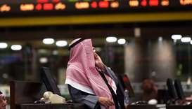 A Kuwaiti trader follows stock prices at Boursa Kuwait stock market in Kuwait City on January 6.