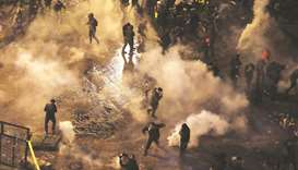Lebanese anti-government protesters scurry away to avoid tear gas as security forces attempt to disp
