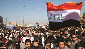 Iraqi demonstrators wave the national flag during an anti-government rally in the southern city of B