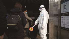 Security personnel wearing protective clothing to help stop the spread of a deadly virus, stands at