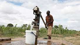 A man pumps water from a borehole to feed his wilting crops during prolonged drought in Bulawayo