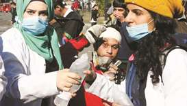 Iraqi medical aid volunteers help an anti-government protester suffering from tear gas effects durin
