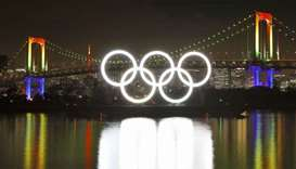 Fireworks light up the sky near the illuminated Olympic rings at a ceremony to mark six months befor