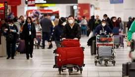 Travellers are seen wearing masks at the international arrivals area
