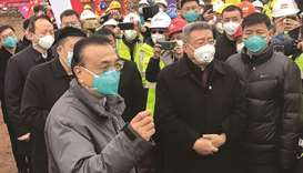 China's Premier Li Keqiang (left) speaks as he visits a construction site of a new hospital being bu