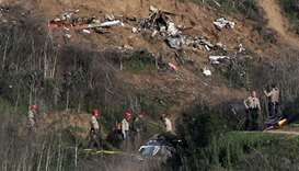 Sheriffs and officials investigate the helicopter crash site of NBA star Kobe Bryant in Calabasas, C