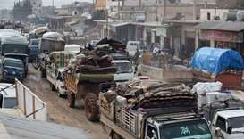 A convoy of trucks transporting the families and belongings of displaced Syrians drives through Haza