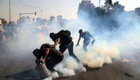 Demonstrators throw tear gas back during ongoing anti-government protests in Baghdad