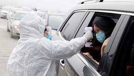 A medical worker in protective suit checks the body temperature of a car passenger at a checkpoint