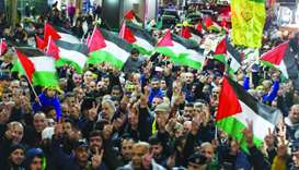 Palestinians take part in a demonstration in the West Bank city of Nablus to protest against US Pres