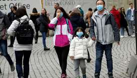 Tourists wearing protective masks walk past the Colosseum, after two cases of coronavirus were confi