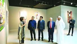 Artist Nameer Qassem explains about the exhibition to Katara general manager Dr Khalid bin Ibrahim a
