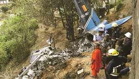 Rescue workers inspect the wreckage of a Sri Lankan air force plane that crashed in Haputale yesterd