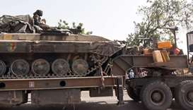 A soldier of the Chad Army sits on top of a tank that is transported on a truck in N'Djamena on Janu