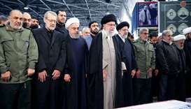 Iran's Supreme Leader Ayatollah Ali Khamenei and Iranian President Hassan Rouhani pray near the coff