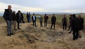 Residents look at a crater caused by a missile launched by Iran on U.S.-led coalition forces on the