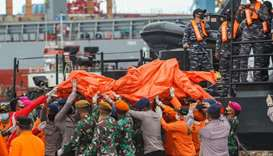 Rescue workers carry recovered debris at the port in Jakarta during the search operation for Sriwija