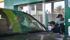 Saudi customs officials check the documents of a visitor travelling by car into Saudi Arabia from Qa