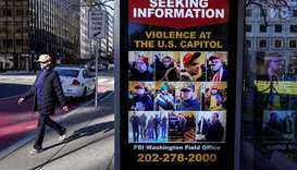 A pedestrian walks past a sign at the bus stop from the FBI seeking information on supporters of US
