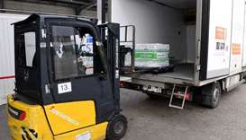A worker unloads from a truck a special box containing the first shipment of Moderna's Covid-19 vacc