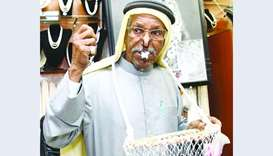 Saad Ismail al-Jassim poses with a clip on his nose and a net basket around his neck.