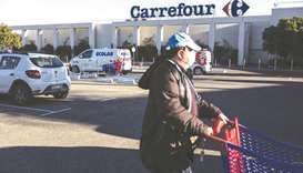A customer wheels a shopping cart outside a Carrefour hypermarket in Avignon, France. On Wednesday,