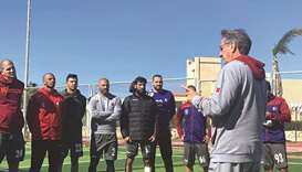Qatar coach Valero Rivera (right) speaks to his players yesterday.