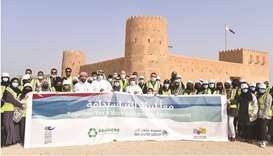 CNA-Q students and officials gather in front of Al Zubarah fort for the clean-up.