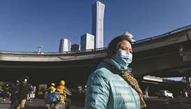 A woman crosses a street in the central business district (CBD) of Beijing on Monday. Gross domestic