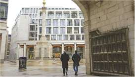 Pedestrians pass the London Stock Exchange in the square mile financial district of the City of Lond