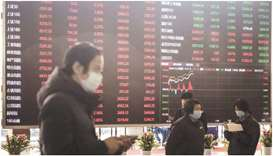 Employees and visitors walk past an electronic stock board at the Shanghai Stock Exchange. The Compo