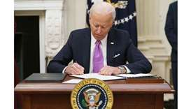 US President Joe Biden signs executive orders as part of the Covid-19 response in the State Dining R