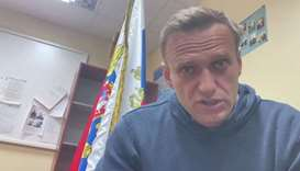 Russian opposition leader Alexei Navalny speaks as he waits for a court hearing in a police station