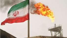 A gas flare on an oil production platform in the Soroush oil fields is seen alongside an Iranian fla