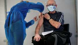 An elderly man, over 75 years of age, receives a dose of the Pfizer-BioNTech Covid-19 vaccine at a c