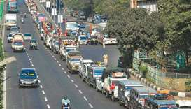 Vehicles carrying farmers cross a state highway during a rally to Mumbai in support of the ongoing f