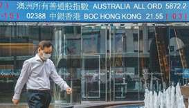 A pedestrian walks past a stock ticker at the Exchange Square complex, which houses the Hong Kong St