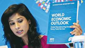 Gita Gopinath, IMF's chief economist, holds up a copy of the World Economic Outlook while speaking a