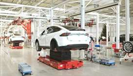 A Tesla Model X SUVs on hydraulic platforms during assembly for the European market at the Tesla Mot