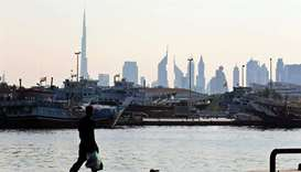 A man walks at the Dubai creek (file). Forecasts for economic recoveries in the six-member Gulf Coop
