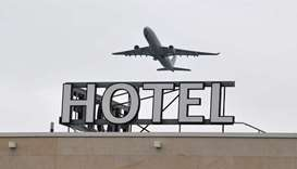 An airplane is seen flying over a hotel at Heathrow Airport in west London